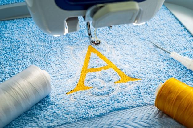 Design de logotipo do alfabeto na toalha no aro da máquina de bordar Foto Premium