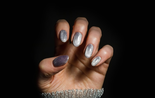 Design de unhas. mãos com manicure de natal de prata brilhante no fundo preto. feche de mãos femininas. art nail. Foto Premium