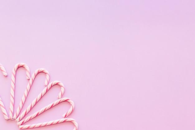 Design feito com bastão de doces de natal no canto de fundo-de-rosa Foto gratuita