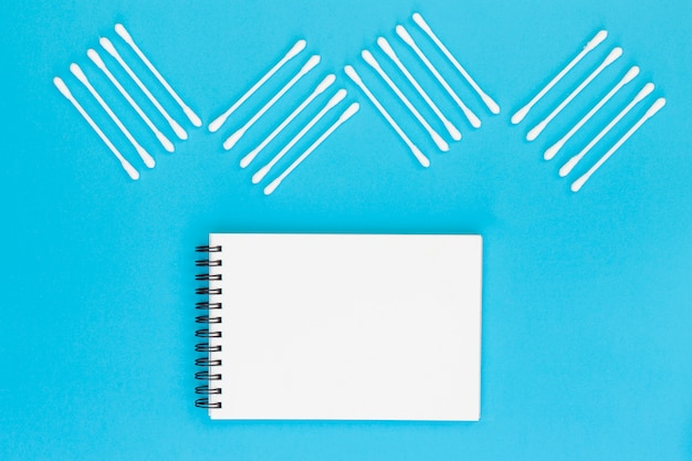 Design feito com cotonetes no bloco de notas espiral em branco sobre fundo azul Foto gratuita