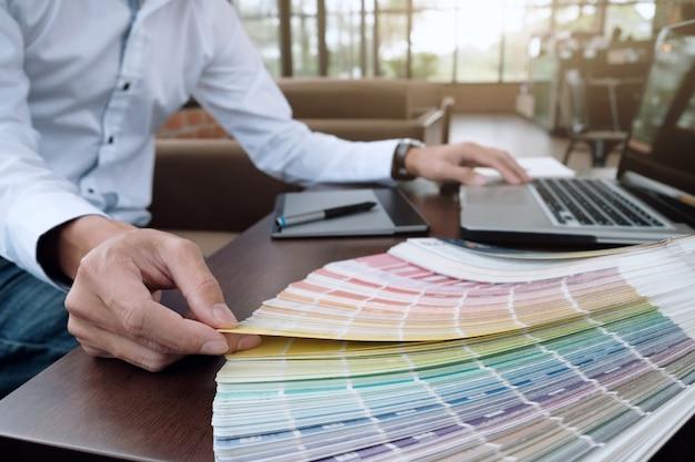 Design gráfico e amostras de cores e canetas em uma mesa. desenho arquitetônico com ferramentas de trabalho e acessórios. Foto gratuita