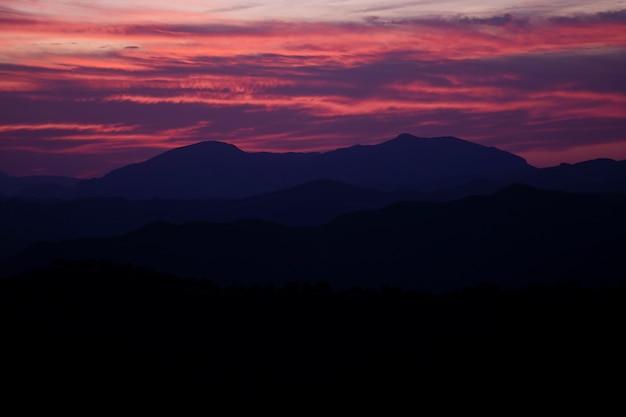 Design lindo céu violeta e vermelho com montanhas Foto gratuita