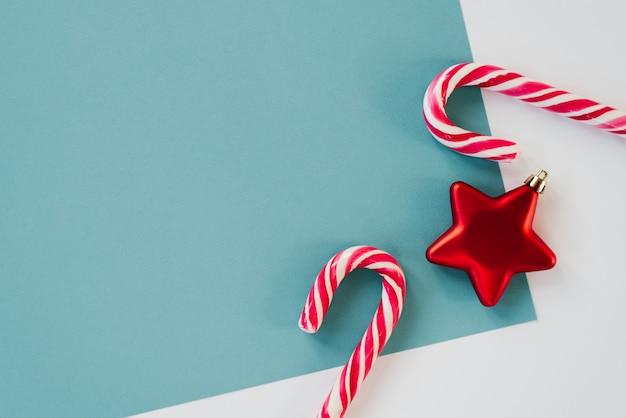 Design minimalista para cartão de natal e ano novo com copyspace. estrela vermelha do brinquedo da árvore de natal e dois bastões de doces nos fundos brancos e azuis. tendência e estilo Foto Premium