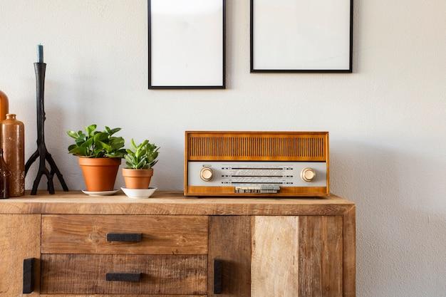 Design retrô da sala de estar com armário e rádio, juntamente com plantas verdes e moldura em branco, parede branca Foto Premium