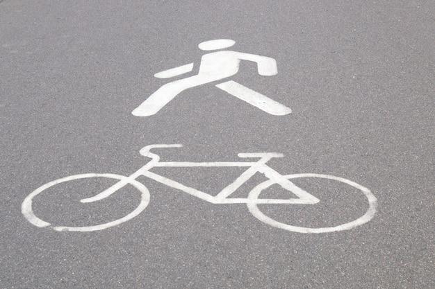 Designação de uma ciclovia e passarela de pedestres pintada em tinta branca no asfalto Foto Premium