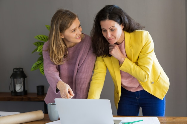 Designer de interiores feminino e cliente usando o computador portátil Foto gratuita