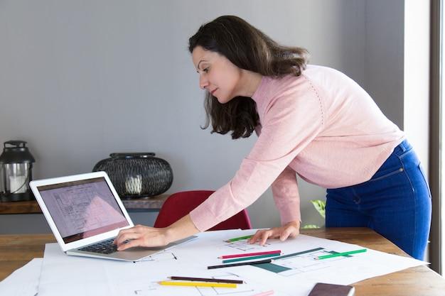 Designer de interiores focado trabalhando no projeto de renovação Foto gratuita