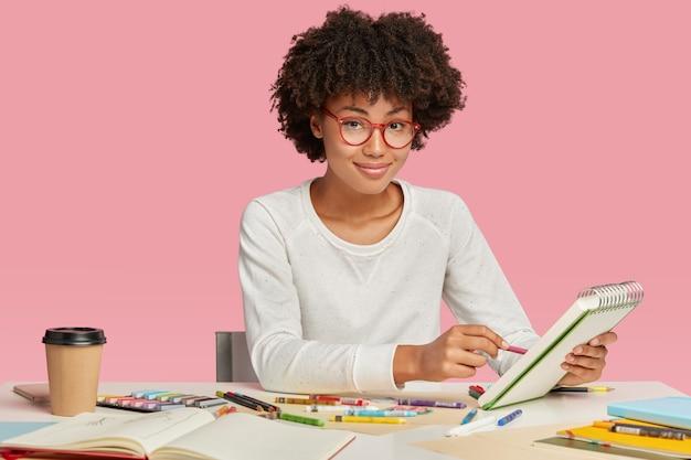 Designer de interiores ou artista gráfico de pele escura faz desenhos em cadernos, tem inspiração para trabalhar Foto gratuita