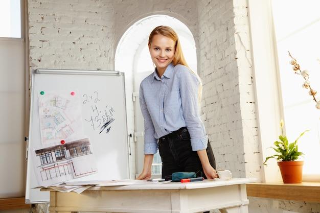 Designer de interiores profissional trabalhando com desenhos de salas em um escritório moderno Foto gratuita
