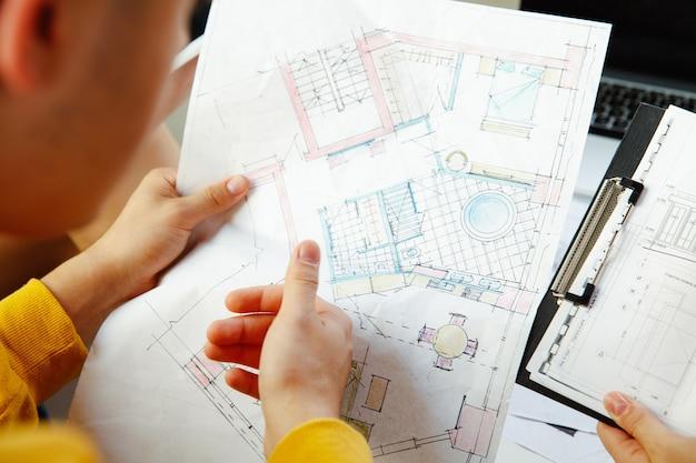 Designer de interiores trabalhando com jovem casal. família adorável e designer ou arquiteto profissional discutindo o conceito do futuro interior, trabalhando com paleta de cores, desenhos de quartos em um escritório moderno. Foto gratuita