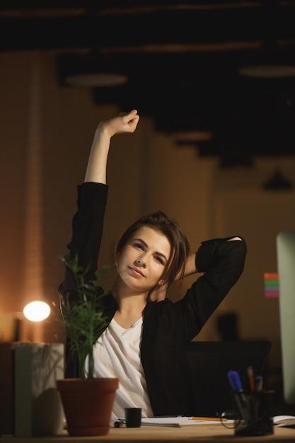 Designer de jovem cansado sentado no escritório à noite Foto gratuita