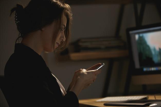 Designer de jovem sério sentado dentro de casa à noite conversando Foto gratuita