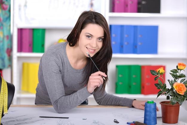 Designer de moda desenho esboço e sorrindo. Foto Premium