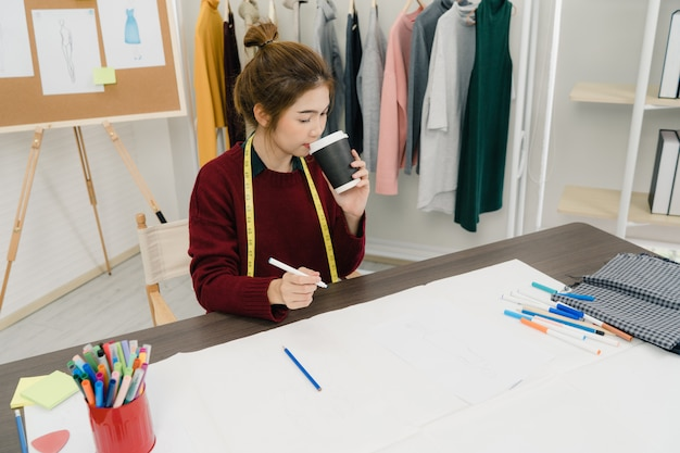 Designer de moda feminina asiática bonita profissional trabalhando com esboços de tecido Foto gratuita