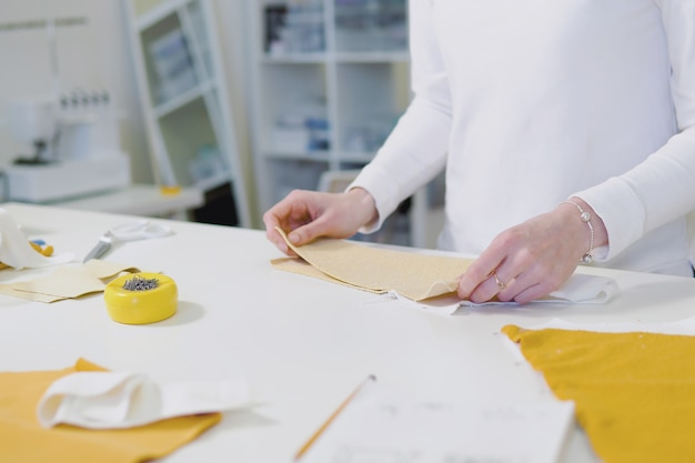 Designer de moda ou tecido de corte sob medida enquanto trabalha com esboço de desenho e material na mesa de trabalho Foto Premium