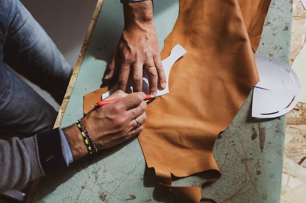 Designer de sapatos trabalhando com couro. Foto Premium