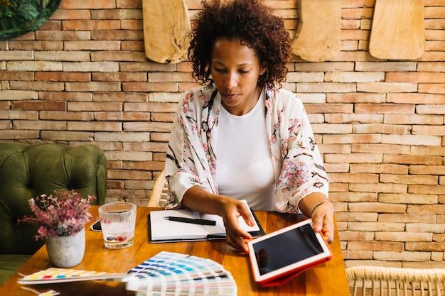 Designer gráfico feminino olhando para amostras de cores segurando o tablet digital na mão Foto gratuita