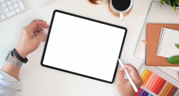 Designer gráfico mão trabalhando com lápis de caneta e desenho tablet no escritório Foto Premium