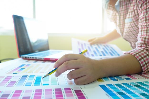 Designer gráfico no trabalho. amostras de amostras de cores. Foto gratuita