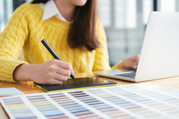 Designer gráfico trabalhando com amostras de cores para seleção. Foto Premium
