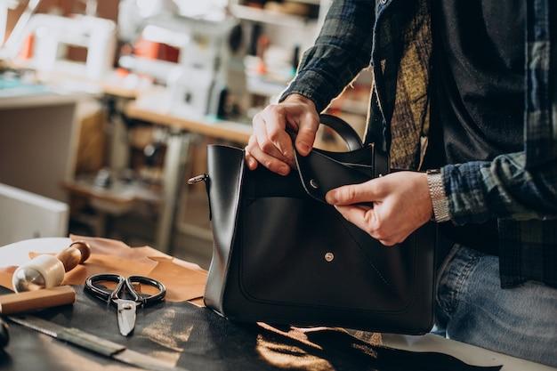 Designer masculino e alfaiate de couro trabalhando em uma fábrica de perto Foto gratuita