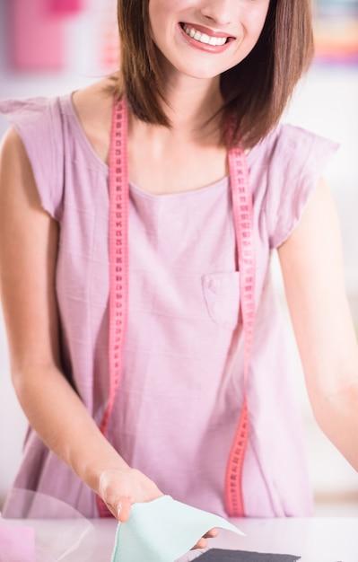 Designer trabalhando com pedaço de tecido na mesa e sorrindo. Foto Premium