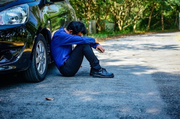 Desiludido homem segurando o telefone inteligente e sentado no carro estacionado na estrada Foto Premium