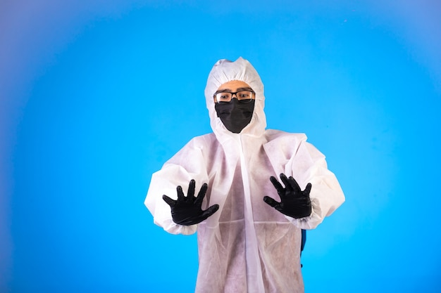 Desinfetante em uniforme preventivo especial e máscaras pretas faz sinais de stop com as duas mãos Foto gratuita