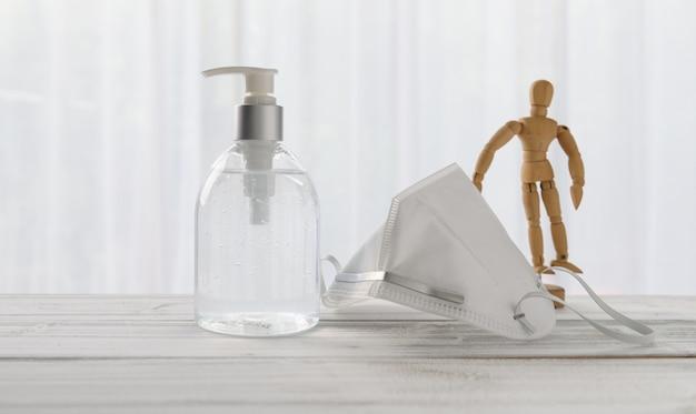 Desinfetante para as mãos, máscara cirúrgica, boneca de madeira na mesa de madeira com fundo branco macio enquanto a quarentena em casa covid-19. Foto Premium