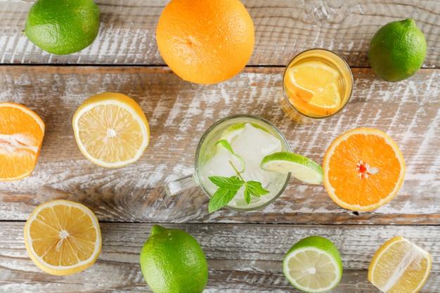 Desintoxicação de água com limas, limões, laranjas, hortelã no copo e copo na superfície de madeira, plana leigos. Foto gratuita