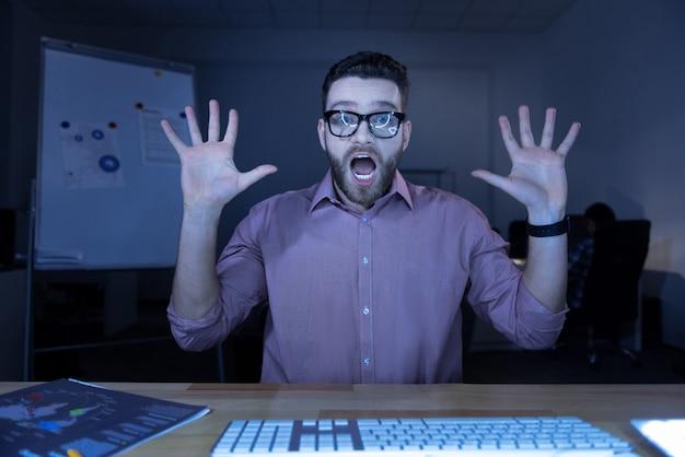 Desisto. homem agradável e emocional agradável sentado à mesa com as mãos levantadas enquanto tem medo de alguma coisa Foto Premium