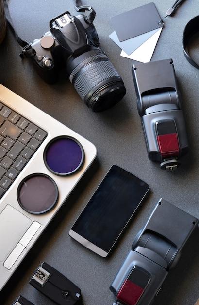 Desktop com equipamento fotográfico, câmera, tripé, flash e computador Foto Premium
