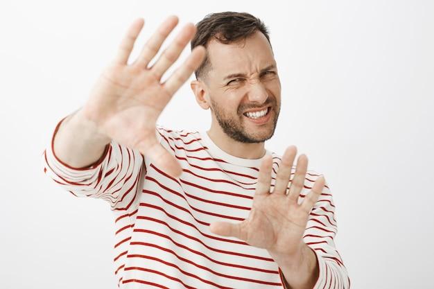 Desligue a luz que é brilhante. homem adulto bonito desconfortável e descontente em roupa listrada puxando as mãos para proteger o rosto, fazendo careta de desconforto Foto gratuita