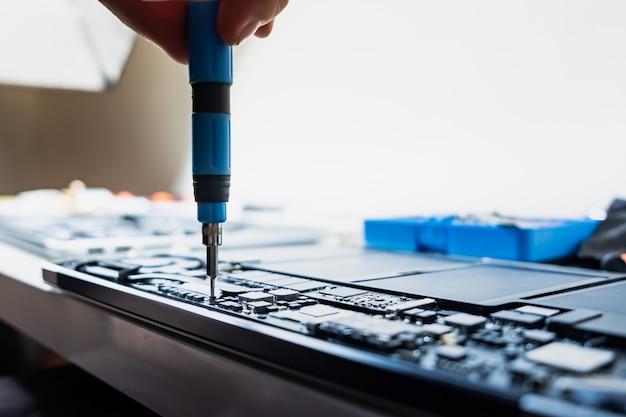 Desmontar um laptop em um serviço profissional. a pessoa realiza serviços regulares e desaparafusa partes de um computador portátil moderno Foto Premium