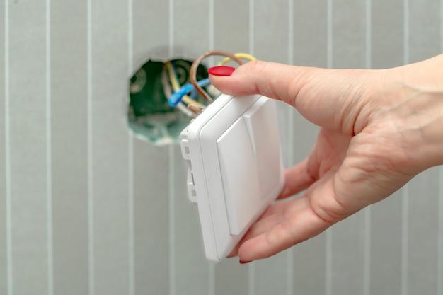 Desmonte o interruptor na mão feminina Foto Premium
