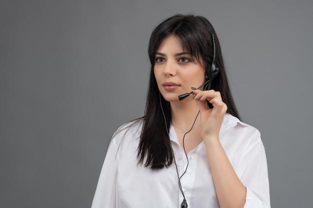 Despachante com fone de ouvido respondendo a perguntas do cliente em um call center isolado Foto Premium