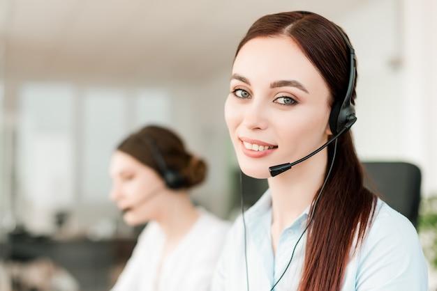 Despachante feminina atraente atendendo chamadas de negócios no escritório da empresa moderna Foto Premium