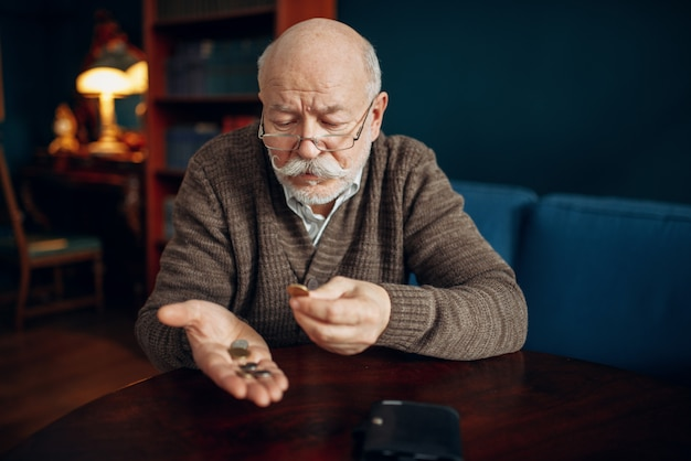 Despeje homem idoso com moedas Foto Premium