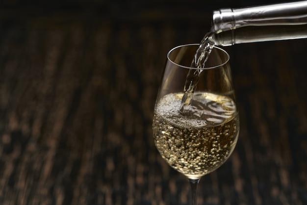 Despeje o vinho branco em um copo na mesa de madeira preta, close-up. Foto Premium