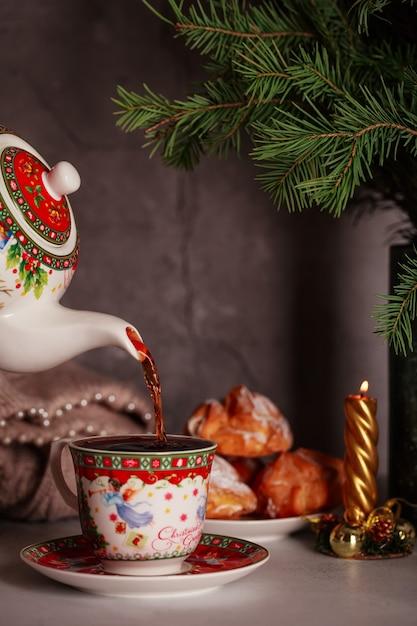 Despeje um chá delicioso de um bule de natal com bolos e galhos de pinheiro Foto Premium