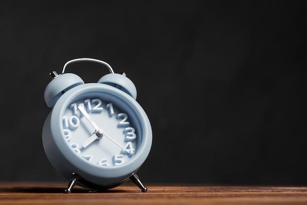 Despertador azul caindo na mesa de madeira contra o fundo preto Foto gratuita