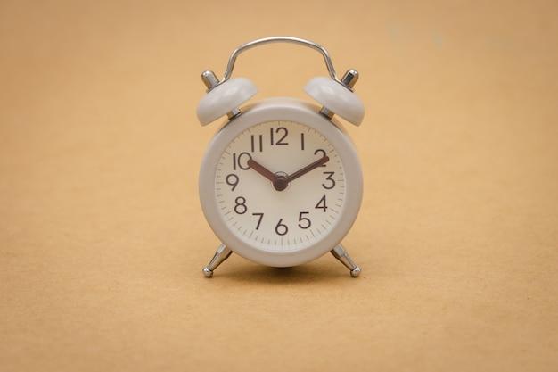 Despertador branco do vintage no conceito marrom do curso do fundo do tempo Foto Premium