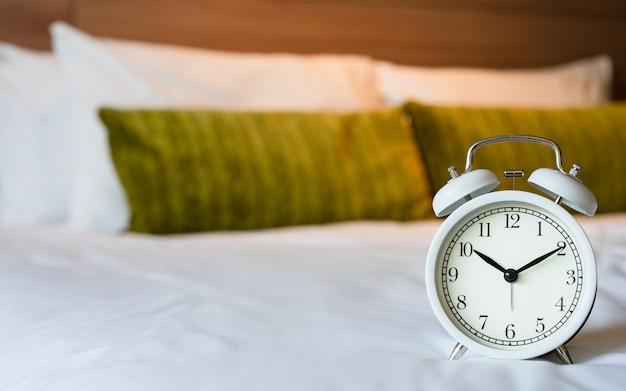 Despertador branco do vintage no quarto. Foto Premium