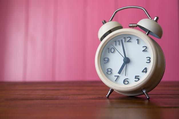 Despertador branco é colocado no quarto rosa. Foto Premium