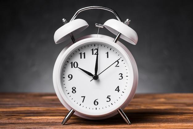 Despertador branco na mesa de madeira texturizada mostrando 10'oclock Foto gratuita