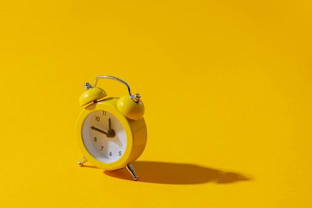 Despertador com dois sinos em fundo amarelo Foto Premium