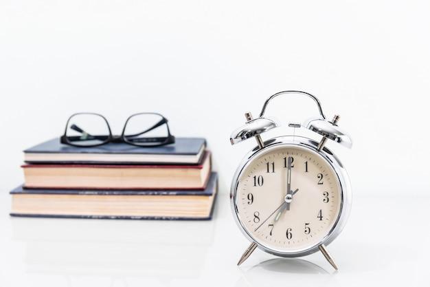 Despertador com livro antigo com óculos Foto Premium