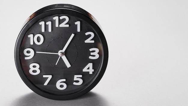 Despertador de forma redonda preta sobre fundo cinza Foto gratuita