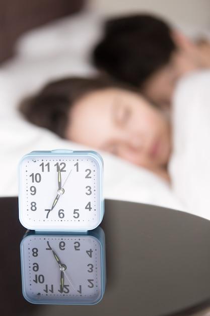 Despertador e casal dormindo no início da manhã, vertical Foto gratuita