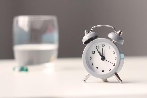 Despertador e comprimidos médicos na tabela de cabeceira. Foto Premium